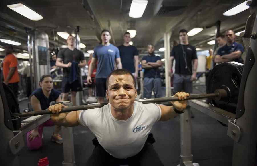 Homem com cara de dor levantando peso. Outras pessoas observam ele ao fundo.