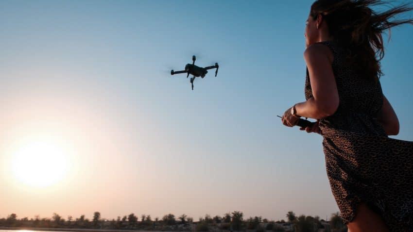 Imagem mostra uma mulher segurando o controle remoto de um drone.