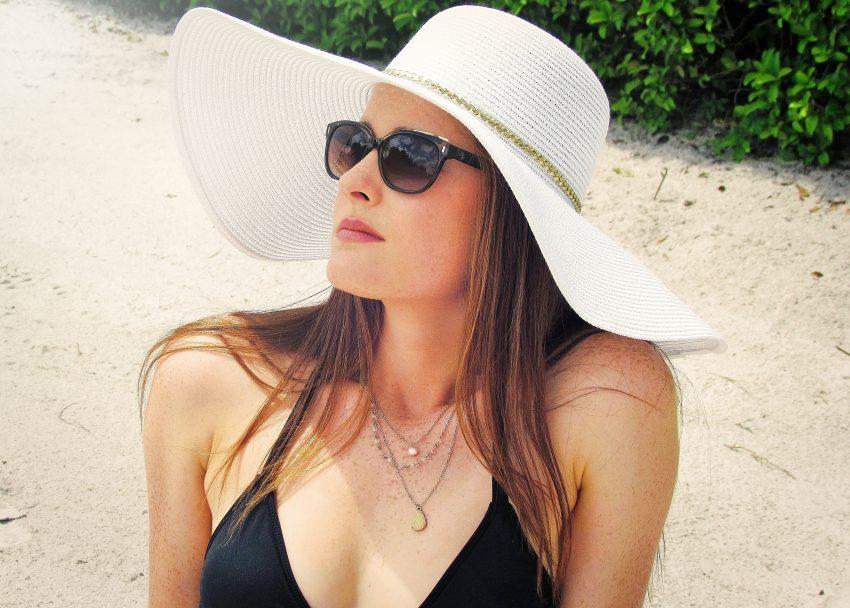 Imagem de uma mulher tomando sol usando um chapéu.