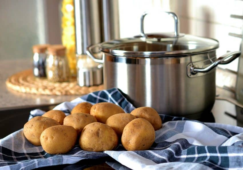 Bancada de cozinha com várias batatas, uma panela de aço inox e potes com condimentos ao fundo.