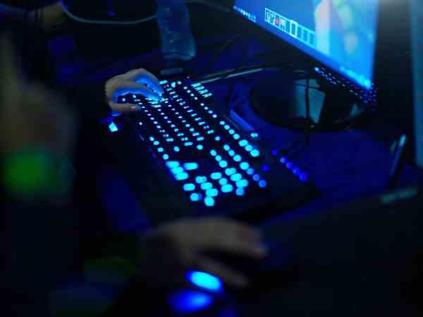 Imagem de pessoa jogando em pc gamer com iluminação azul.