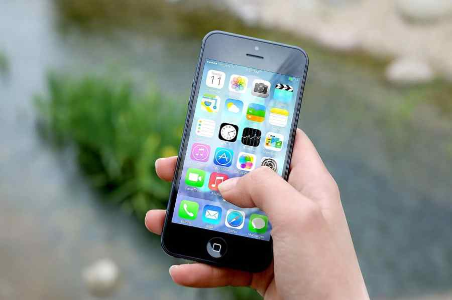 Mão de mulher segurando um iphone ligado no menu principal.