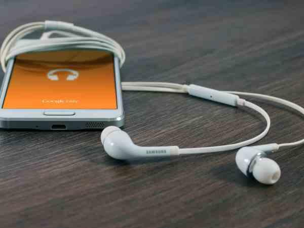 Imagem de smartphone em mesa, com fones de ouvido.