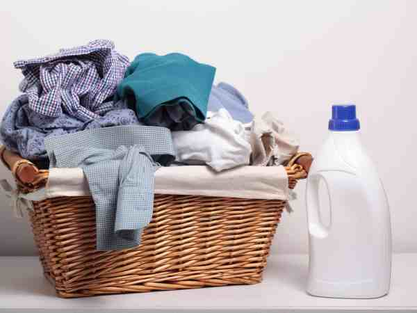 Imagem cesto de roupas de vime com roupas dentro e um produto de limpeza ao lado.