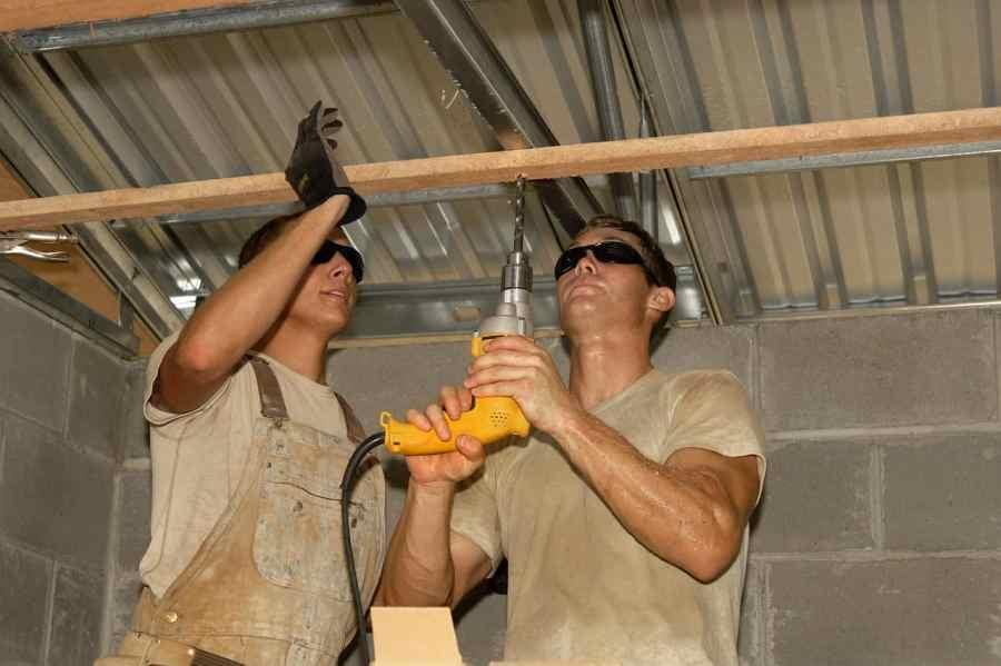 Imagem mostra dois trabalhadores usando uma furadeira para perfurar uma barra de madeira.