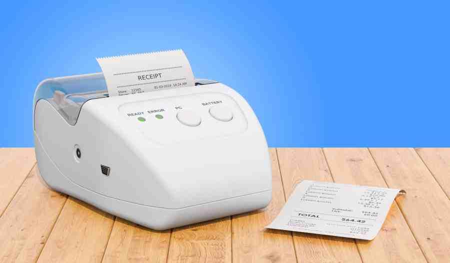 Imagem de impressora sobre mesa com recibo impresso.