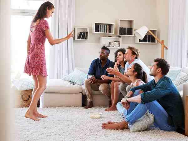 Foto de um grupo de amigos em uma sala de estar brincando de mímica.