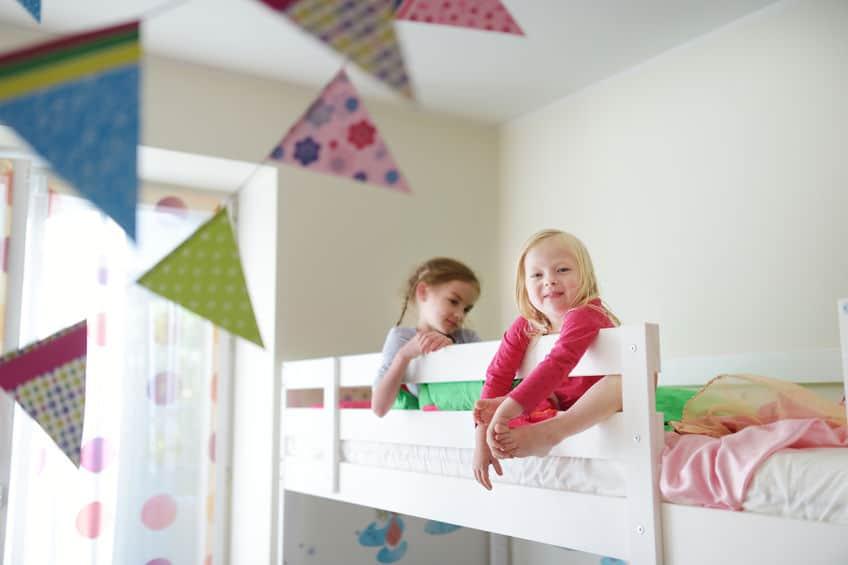 Imagem de duas meninas encostadas na grade de cama.