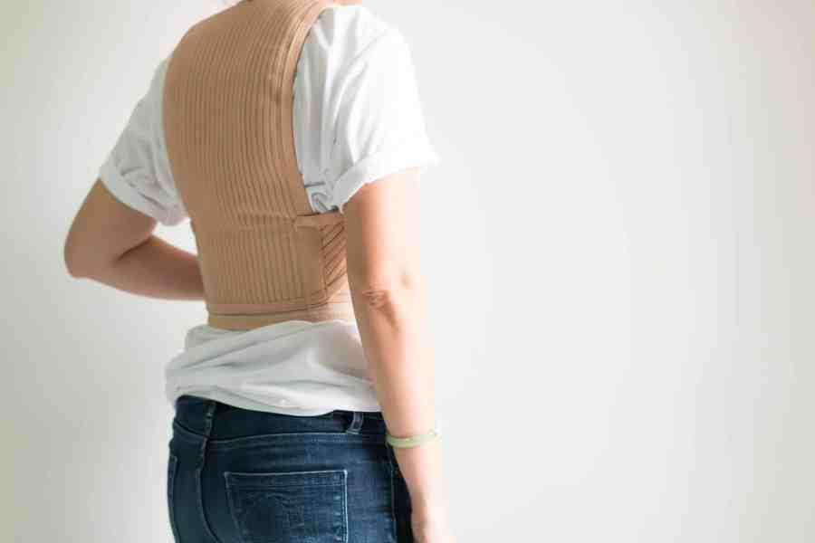 Imagem de mulher de costas com um corretor de coluna bege sobre blusa branca.