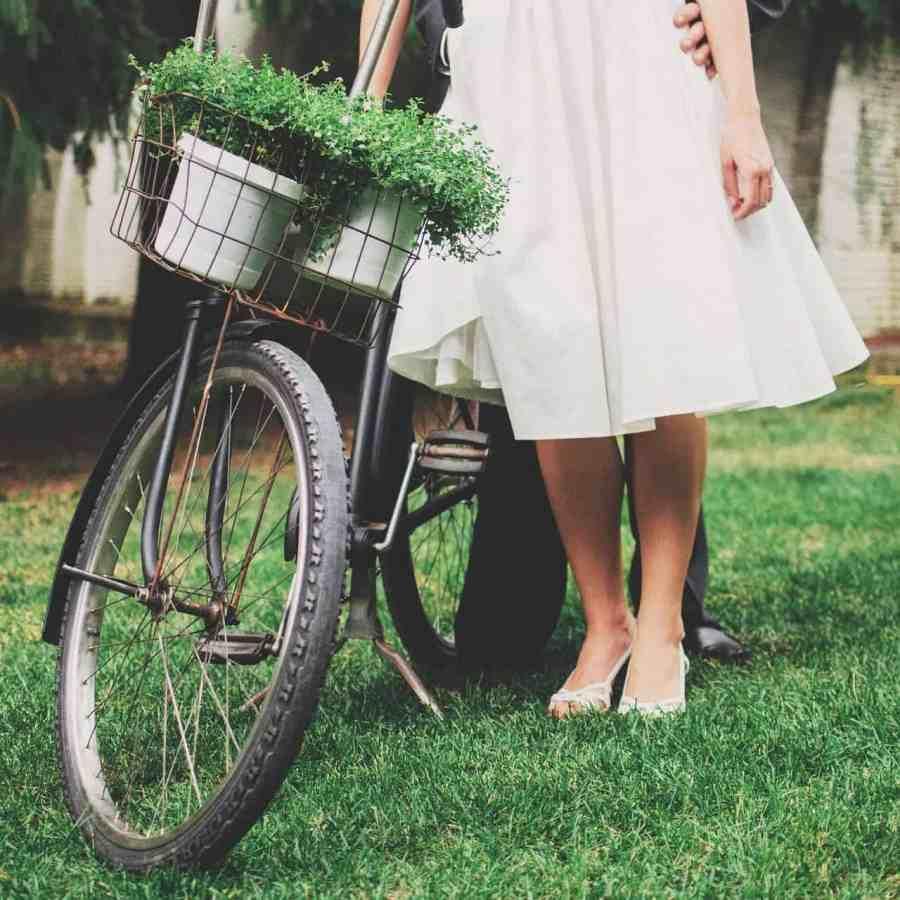 Casal ao lado de uma bicicleta vintage.