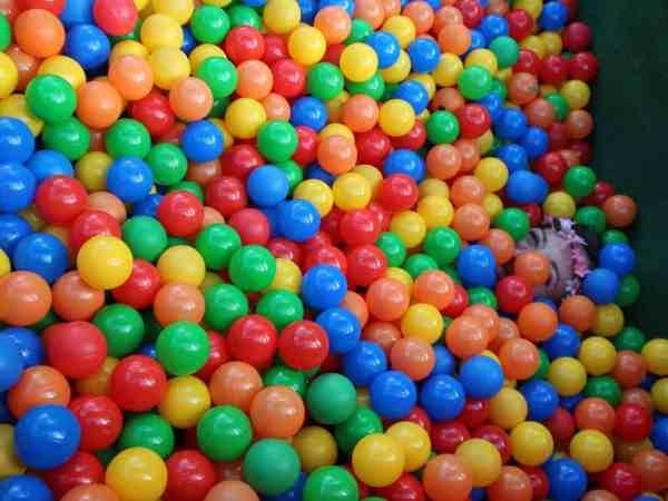 Imagem mostra uma pessoa coberta por bolinhas dentro de uma piscina de bolinhas.