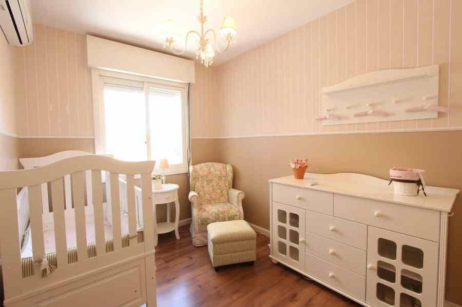 Na foto um quarto de bebê com berço, cômoda e poltrona em bege e rosa.