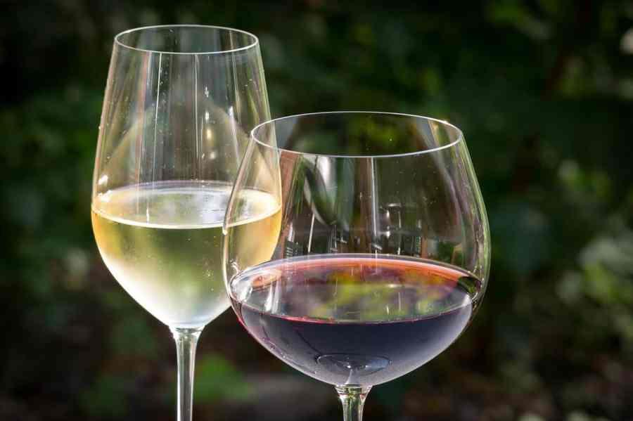 Imagem mostra taça de vinho branco e tinto.