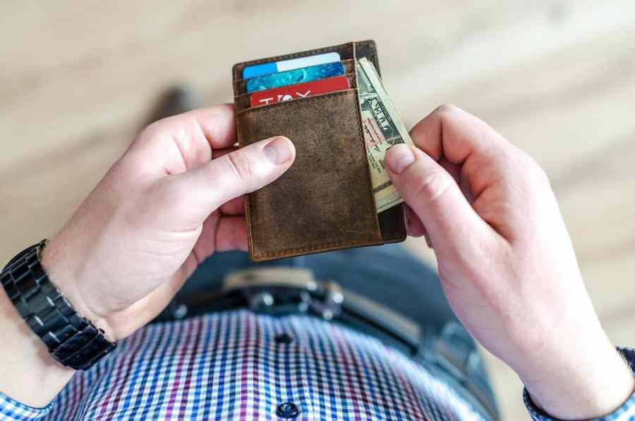 Imagem de homem segurando um porta documentos de couro marrom com dinheiro e cartões de crédito.