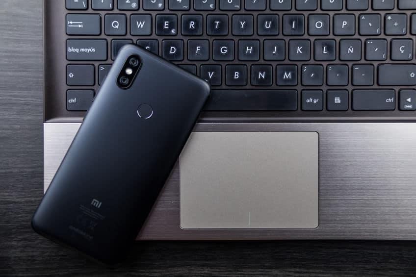 Celular xiaomi preto em cima de laptop.