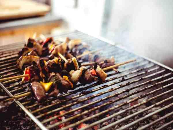 Foto de espetinhos de carne e legumes em uma churrasqueira, com blur ao fundo.