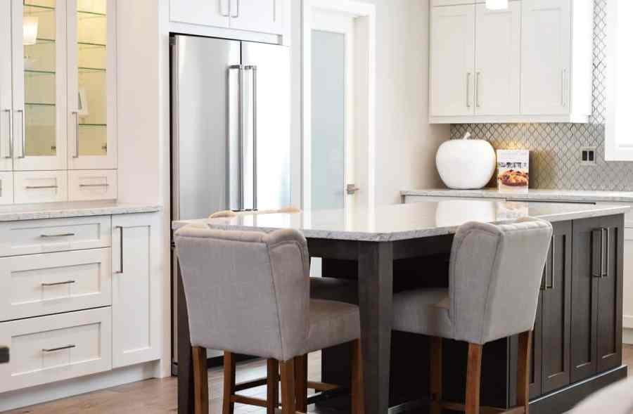 Cozinha moderna e aberta, com mesa, cadeiras cinzas, armários brancos e uma geladeira de inox com duas portas.