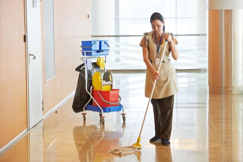 Imagem de uma mulher limpando o chão da corredor com um mop e outros equipamentos para limpeza