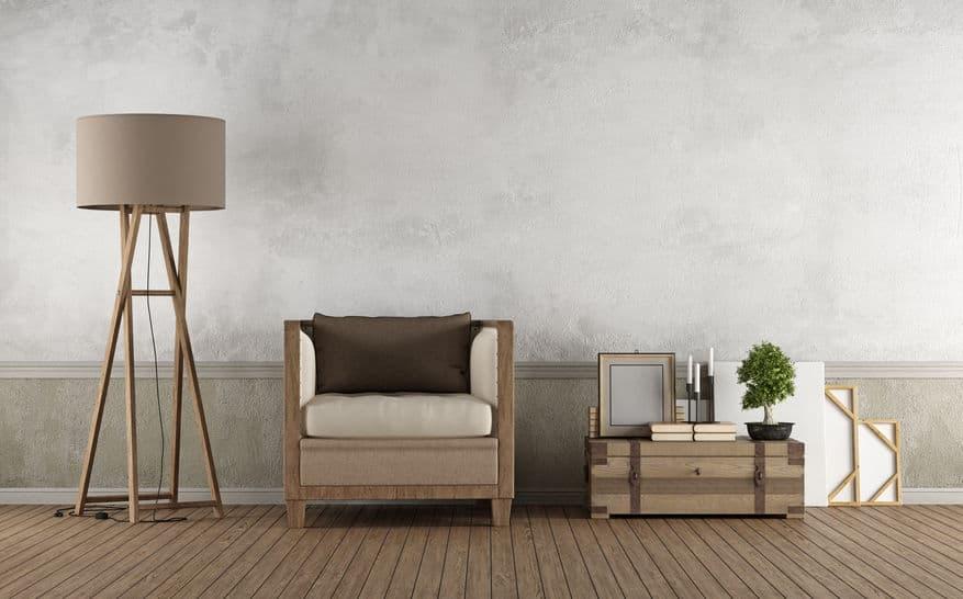 Sala de estar com decoração em madeira e tons de marrom com poltrona, luminária de chão e mesinha lateral.
