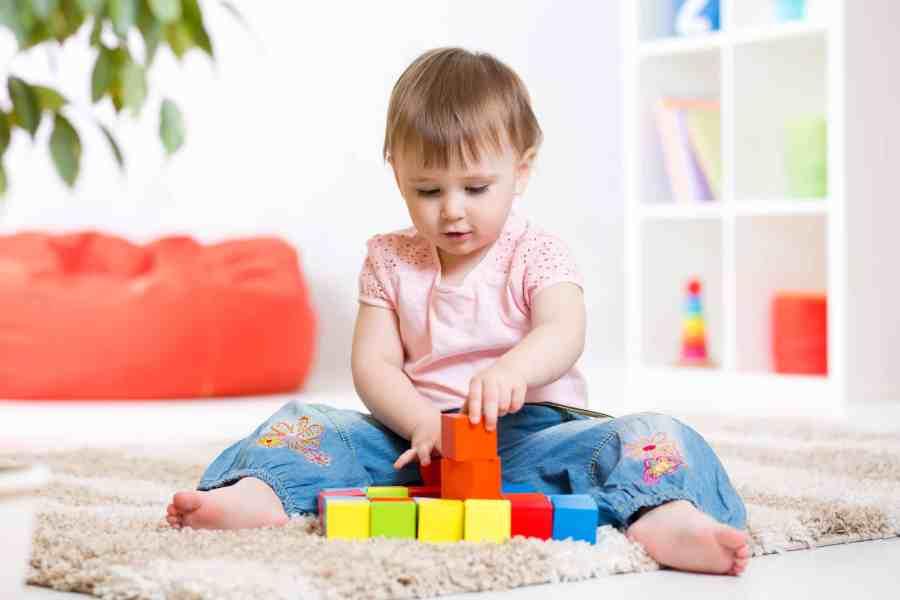 Na foto uma menina sentada em um tapete brincando com blocos de montar.