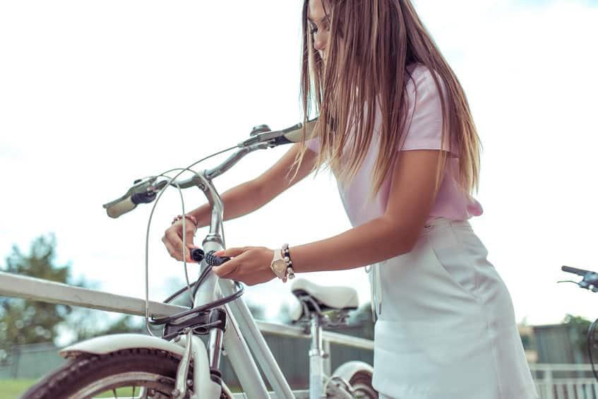 Garota trancando sua bicicleta com cadeado.