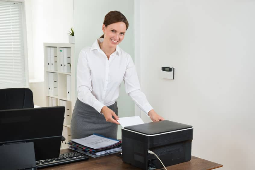 Mulher no escritório usando uma impressora multifuncional com scanner.