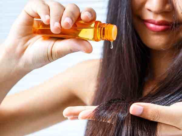 Foto de uma mulher morena, aplicando óleo capilar nos cabelos.