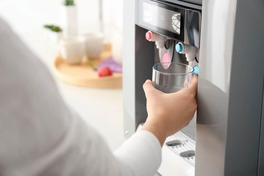 Mão de mulher enchendo copo com água em um purificador na cozinha.