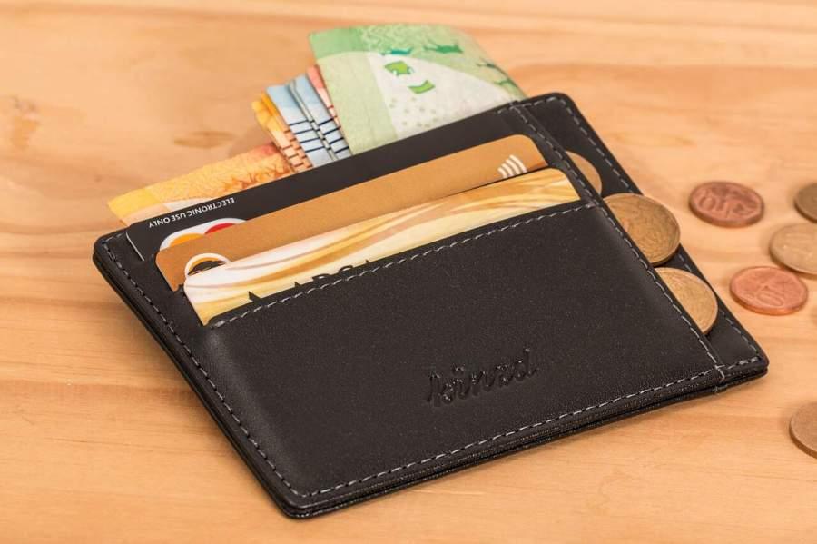 Imagem de porta documentos preto com dinheiro, moedas e cartões de crédito sobre mesa de madeira.