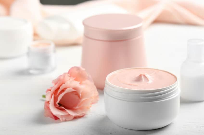 Imagem de potes de creme hidratante sobre mesa com rosa ao lado.