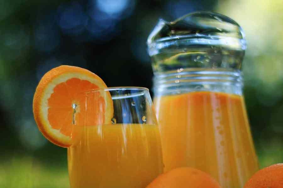 Copo e jarra de vidro com suco de laranja e fatia de laranja decorando o copo.