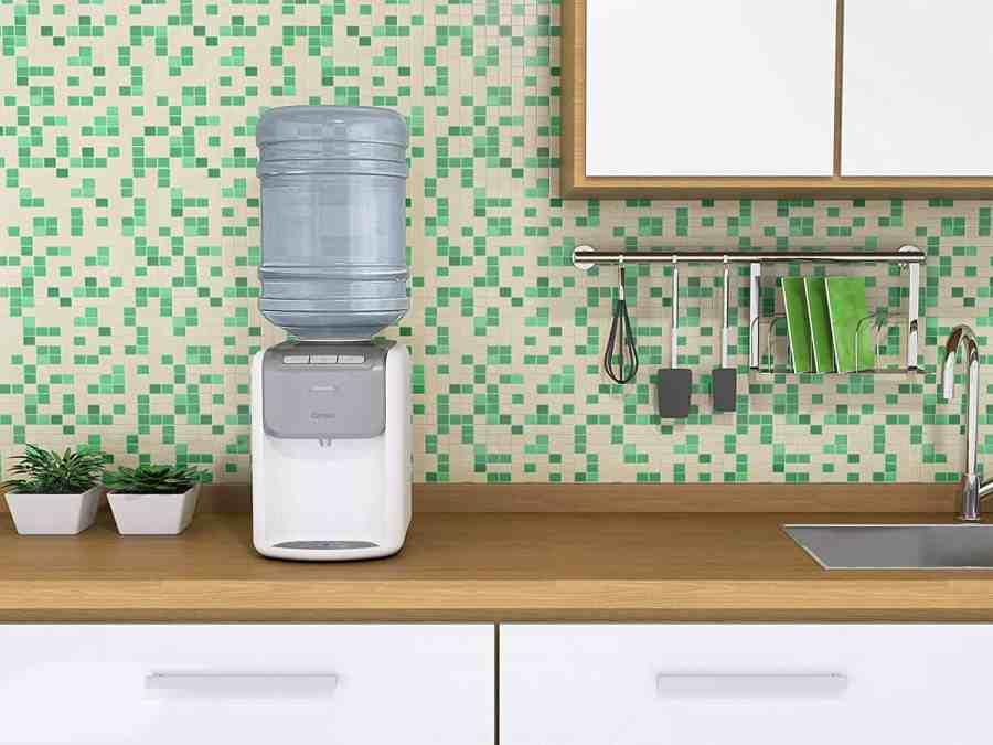 Bebedouro com galão de água em bancada de cozinha.