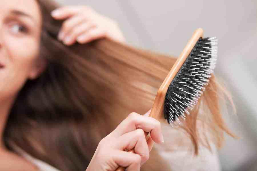Foto de uma mulher escovando o cabelo com escova de madeira plana.