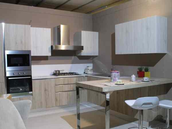 Imagem mostra uma cozinha com um forno elétrico de embutir, uma bancada com duas cadeiras brancas, um fogão e uma pia.