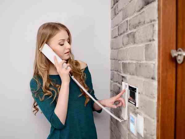 Imagem de uma mulher liberando a entrada de um visitante pelo interfone.