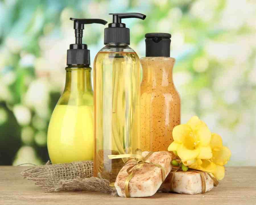 Três frascos de sabonete líquido ao lado de dois sabonetes em barra e flor.