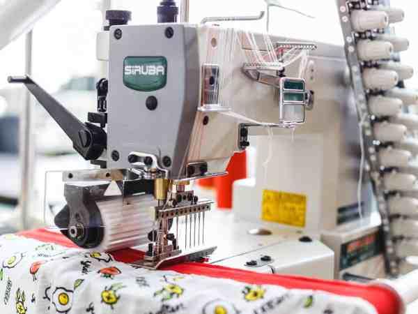 Imagem de máquina de costura realizando o acabamento em tecido.