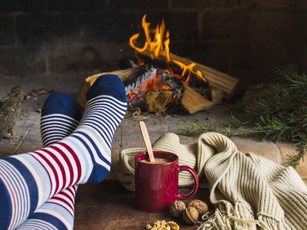 Usando meias listradas, pessoa aquece os pés próxima a lareira.