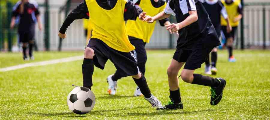 Imagem mostra meninos jogando futebol com colete esportivo.
