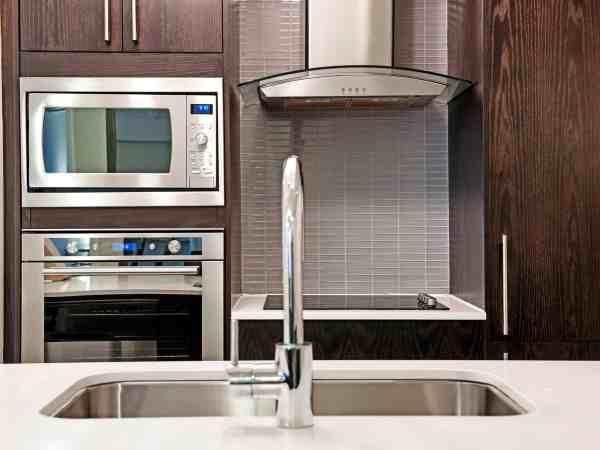 Foto de uma cozinha contendo armários de madeira, micro-ondas de embutir, forno de embutir, cooktop, exaustor e pia.
