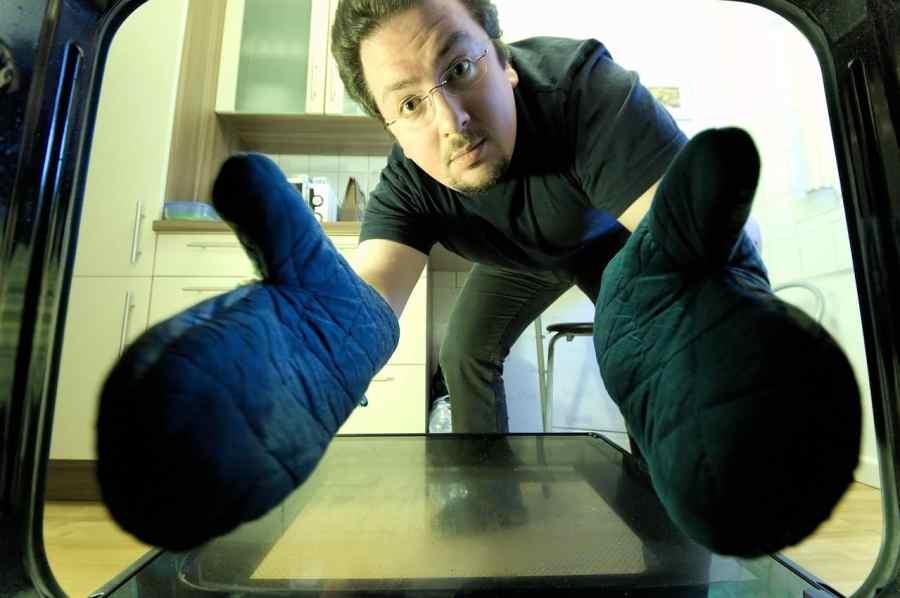 Imagem mostra um homem com luvas retirando alguma coisa do forno.