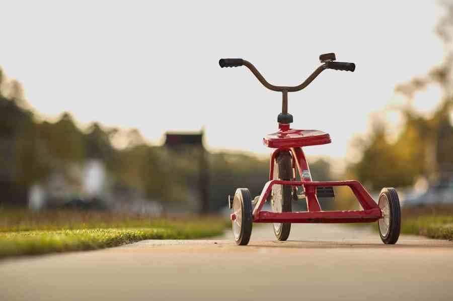 Triciclo infantil vermelho de metal.