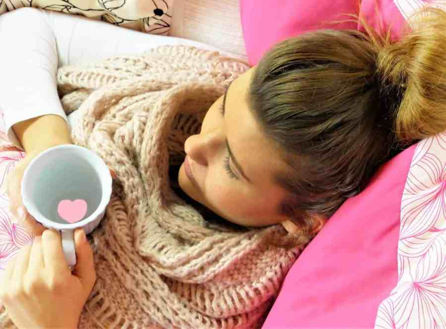 Jovem mulher com uma xícara nas mãos e usando cachecol.