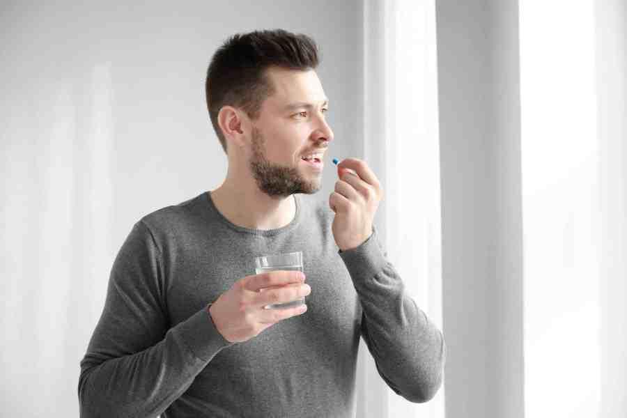 Homem tomando comprimido com copo de água.