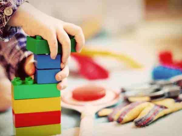 Na foto as mãos de um menino com blusa xadrez encaixando algumas peças coloridas de brinquedo.