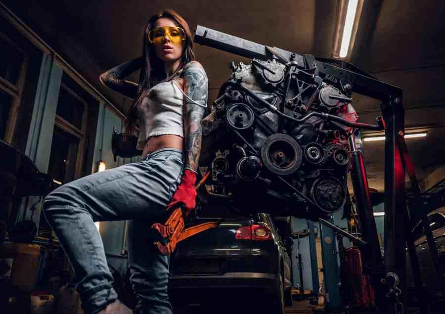 Imagem mostra uma mulher ao lado de um guincho hidráulico que levanta partes de um carro.