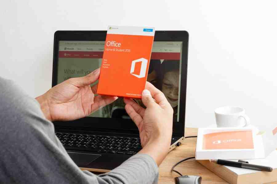Homem segurando pacote do Microsoft Office e notebook ao fundo.