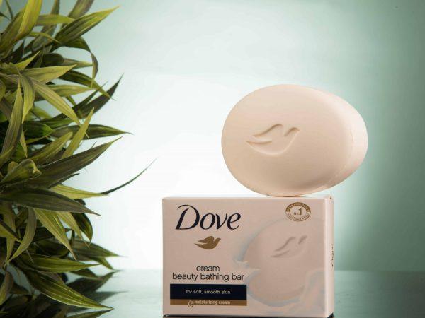 Foto mostra um sabonete Dove em barra em cima da embalagem de papelão. Há uma planta do lado esquerdo.