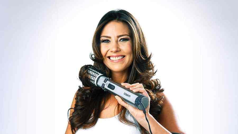 Mulher usando escova rotativa no cabelo.