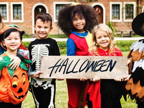 Na foto seis crianças fantasiada segurando uma placa escrito halloween.